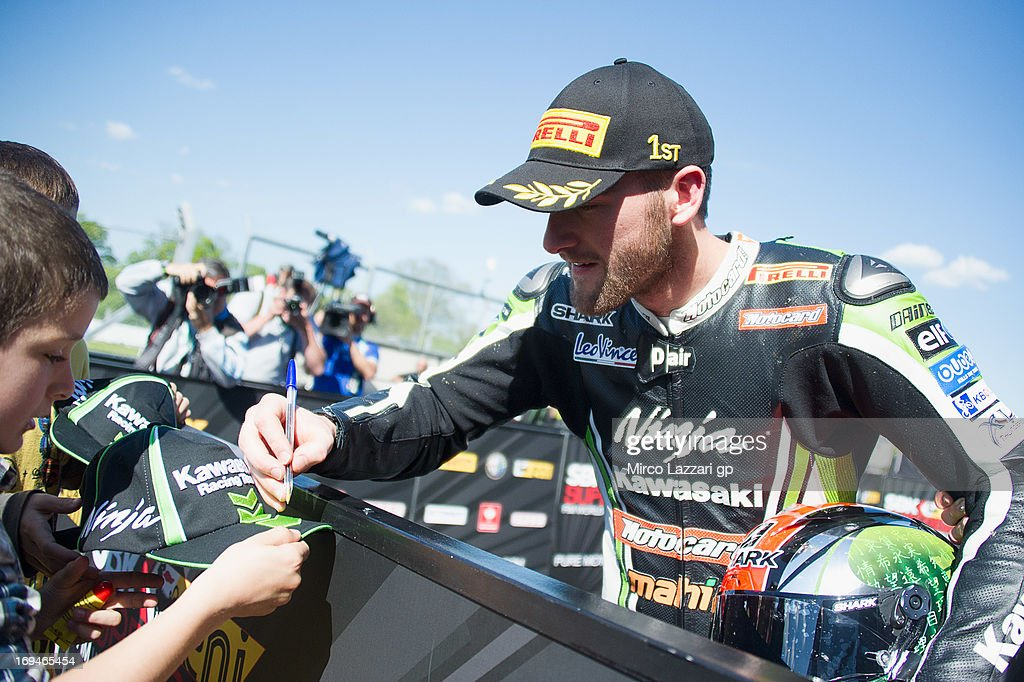 Tom Sykes of Great Britain and Kawasaki Racing Team signs autographs for fans at the end of the Super Pole during the World Superbikes - Qualifying during the round five of 2013 Superbikes FIM World Championship at Donington Park on May 25, 2013 in Castle Donington, England.