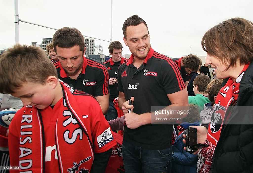 Tom Taylor and Israel Dagg of the Crusaders sign autographs after a media announcement that BNZ will be naming rights sponsor of the Crusaders on July 19, 2013 in Christchurch, New Zealand.
