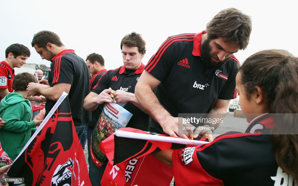 Tom Taylor, Matt Todd and Sam Whitelock of the Crusaders sign autographs after a media announcement that BNZ will be naming rights sponsor of the Crusaders on July 19, 2013 in Christchurch, New Zealand.