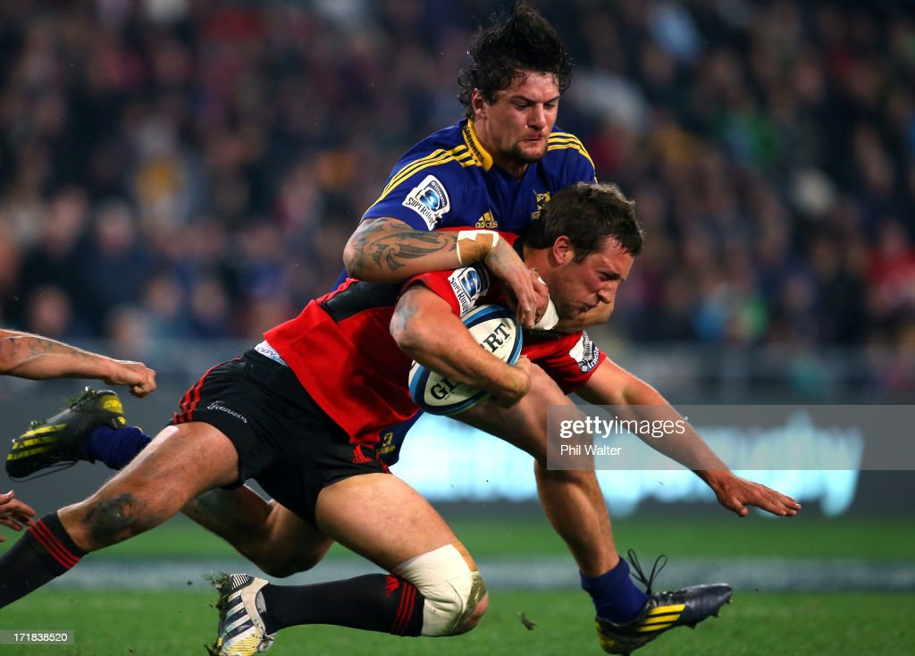 Tom Taylor of the Crusaders is tackled by Elliot Dixon of the Highlanders during the round 18 Super Rugby match between the Highlanders and the Crusaders at Forsyth Barr Stadium on June 29, 2013 in Dunedin, New Zealand.
