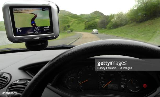 A Tom Tom satellite navigation system is seen attached to a car windscreen