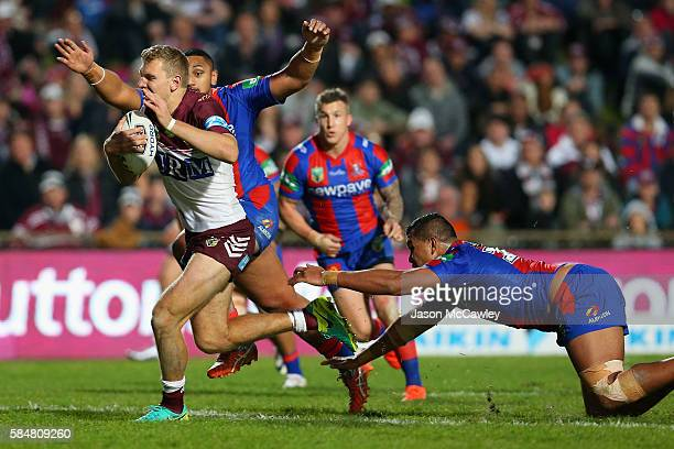 Tom Trbojevic of the Sea Eagles is tackled during the round 21 NRL match between the Manly Sea Eagles and the Newcastle Knights at Brookvale Oval on...