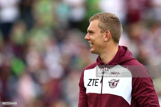 Tom Trbojevic of the Sea Eagles watches his team mates warm up during the round 13 NRL match between the Manly Sea Eagles and the Canberra Raiders at...