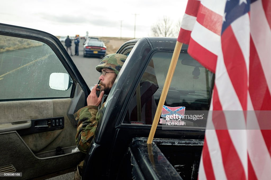 Tom Wagner, a self-described supporter of the movement agains the federal government, takes a smoke break in his truck near the Malheur Wildlife Refuge Headquarters near Burns, Oregon, on February 11, 2016. The FBI surrounded the last protesters holed up at a federal wildlife refuge in Oregon amid reports they will surrender on Thursday, suggesting the weeks-long armed siege is approaching a climax. / AFP / Rob Kerr
