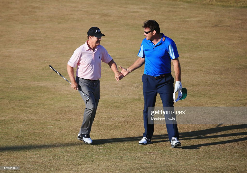 Tom Watson of the United States and Sir Nick Faldo of England shake hands as they walk down the 18th fairway during the second round of the 142nd Open Championship at Muirfield on July 19, 2013 in Gullane, Scotland.
