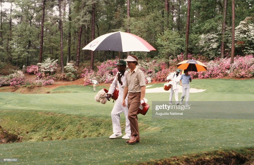 Tom Watson walks off the 13th green with his caddie holding an umbrella during the 1979 Masters Tournament at Augusta National Golf Club on April 15th, 1979 in Augusta, Georgia.