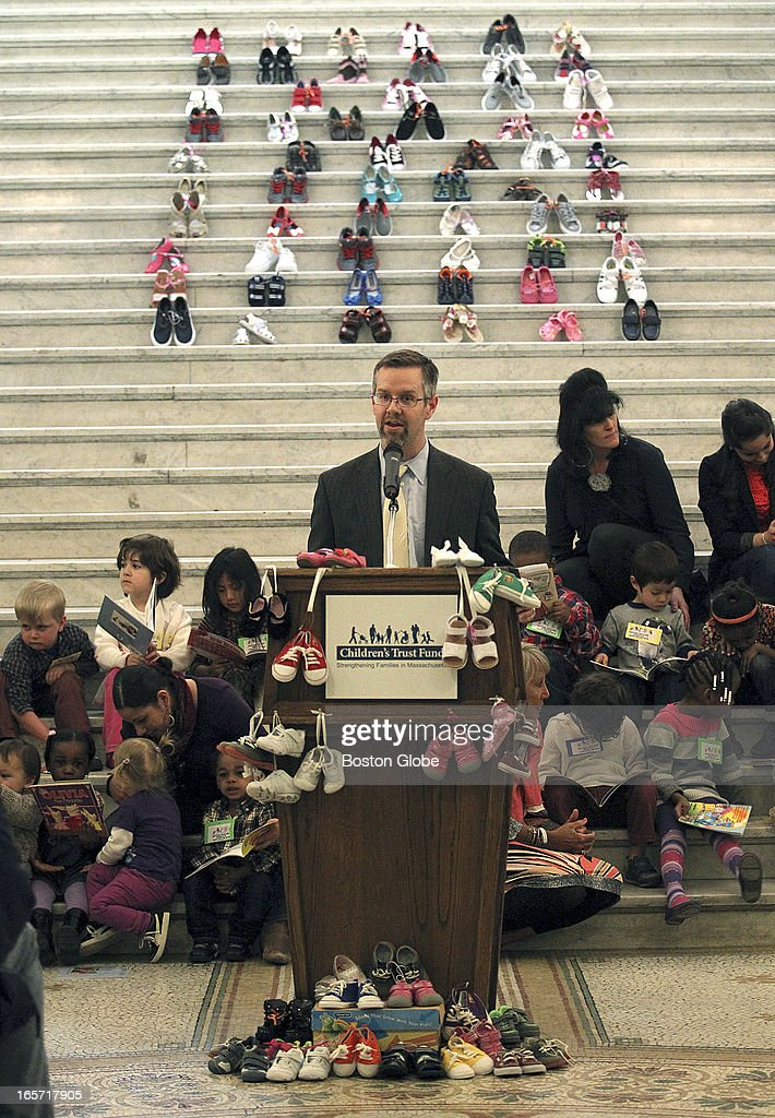 Tom Weber, acting commisioner of the Dept. of Early Education and Care speaks at a press conference in front of children and 69 pair of children's shoes on the Grand Staircase at the State House. Each pair represent the average number of children abused every day in Massachusetts.