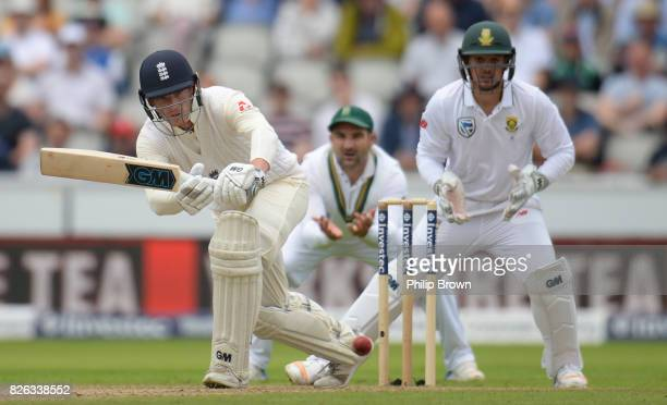 Tom Westley of England hits out watched by Quinton de Kock of South Africa during the 4th Investec Test match between England and South Africa at Old...