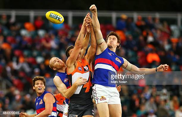Tom Williams and Tom Young of the Bulldogs spoil a mark for Jonathon Patton of the Giants during the round four AFL match between the Greater Western...