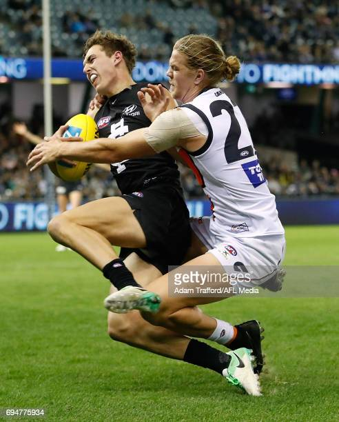 Tom Williamson of the Blues is tackled by Harrison Himmelberg of the Giants during the 2017 AFL round 12 match between the Carlton Blues and the GWS...
