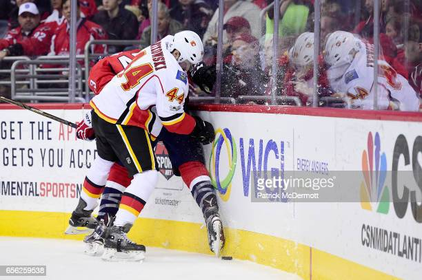 Tom Wilson of the Washington Capitals and Matt Bartkowski of the Calgary Flames collide in the first period during an NHL game at Verizon Center on...