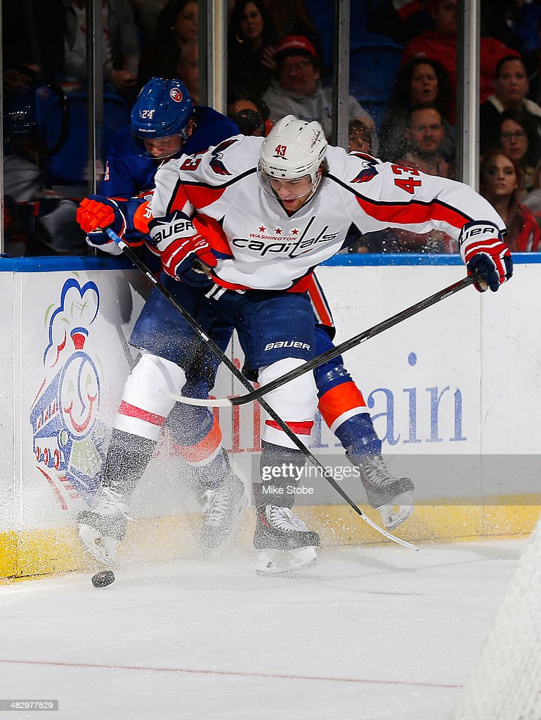 Tom Wilson #43 of the Washington Capitals battles for the puck with Kevin Czuczman #24 of the New York Islanders at Nassau Veterans Memorial Coliseum on April 5, 2014 in Uniondale, New York. The Capitals defeated the Islanders 4-3.