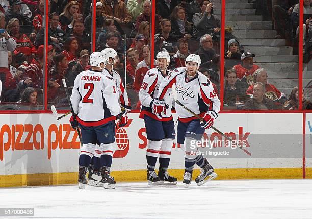 Tom Wilson of the Washington Capitals celebrates the opening goal of the NHL game against the Ottawa Senators with teammates Matt Niskanen and Daniel...