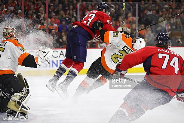 Tom Wilson of the Washington Capitals checks Brandon Manning of the Philadelphia Flyers during the third period at Wells Fargo Center on December 21...