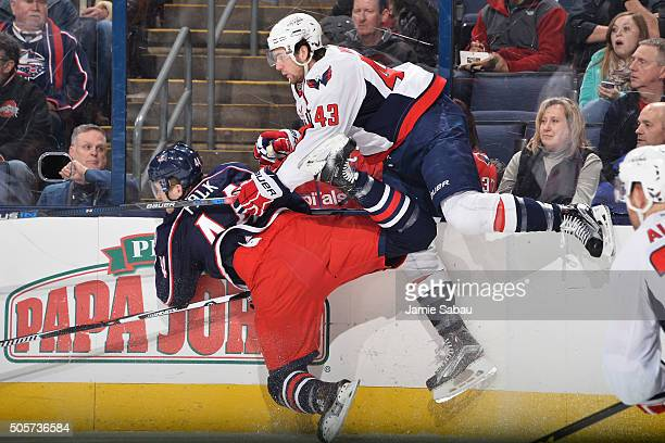 Tom Wilson of the Washington Capitals checks Justin Falk of the Columbus Blue Jackets to the ice during the first period of a game on January 19 2016...