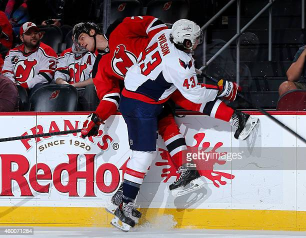 Tom Wilson of the Washington Capitals hits Jon Merrill of the New Jersey Devils in the first period on December 6 2014 at the Prudential Center in...