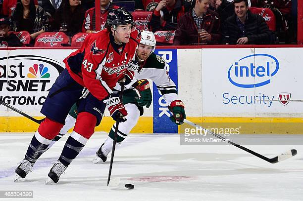 Tom Wilson of the Washington Capitals moves the puck up ice against Kyle Brodziak of the Minnesota Wild in the first period during an NHL game on...