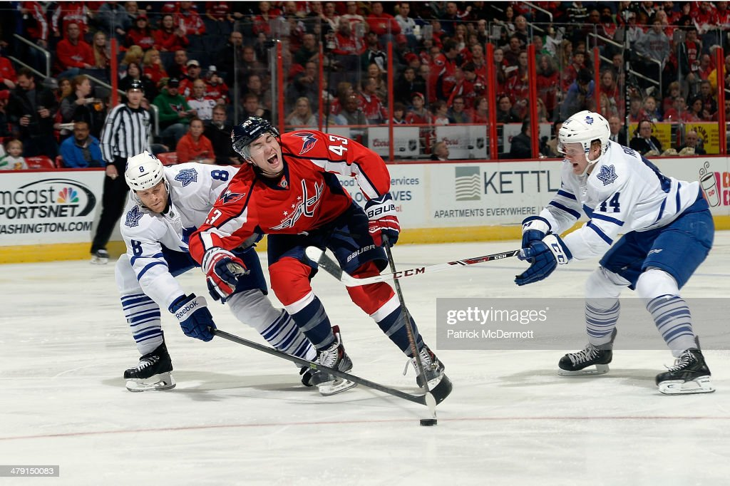 Tom Wilson #43 of the Washington Capitals reacts as he battles for the puck against <a gi-track='captionPersonalityLinkClicked' href=/galleries/search?phrase=Tim+Gleason&family=editorial&specificpeople=211575 ng-click='$event.stopPropagation()'>Tim Gleason</a> #8 and <a gi-track='captionPersonalityLinkClicked' href=/galleries/search?phrase=Morgan+Rielly&family=editorial&specificpeople=8050727 ng-click='$event.stopPropagation()'>Morgan Rielly</a> #44 of the Toronto Maple Leafs in the second period during an NHL game at Verizon Center on March 16, 2014 in Washington, DC.