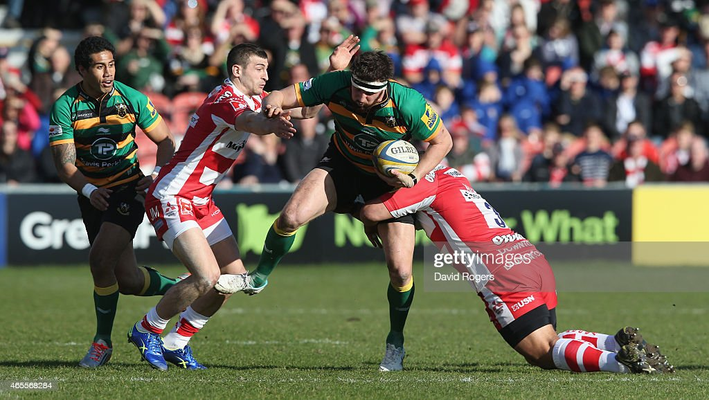 Tom Wood of Northampton is tackled by Jonny May and John Afoa during the Aviva Premiership match between Gloucester and Northampton Saints at...