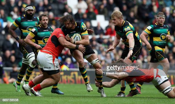 Tom Wood of Northampton is tackled by Titi Lamositele and Michael Rhodes during the Aviva Premiership match between Northampton Saints and Saracens...