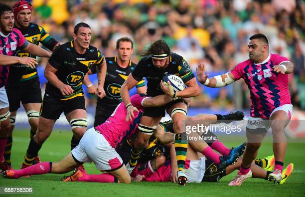 Tom Wood of Northampton Saints is tackled by Paul Alo Emile of Stade Francais during the Champions Cup Playoff Final between Northampton Saints and...