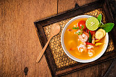 Tom yam kong or Tom yum, Tom yam is a spicy clear soup typical in Thailand and No.1 Thai Dish Cuisine. Tom yam kong on wooden table. Thai food.