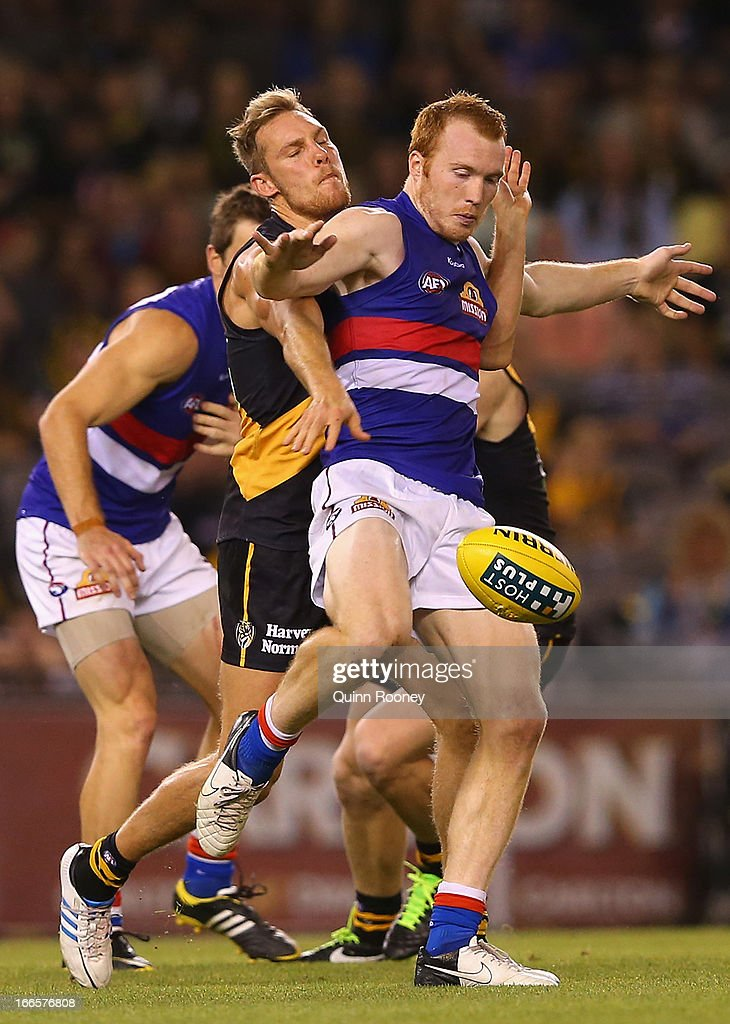 Tom Young of the Bulldogs kicks whilst being tackled by Luke McGuane of the Tigers during the round three AFL match between the Richmond Tigers and the Western Bulldogs at Etihad Stadium on April 14, 2013 in Melbourne, Australia.