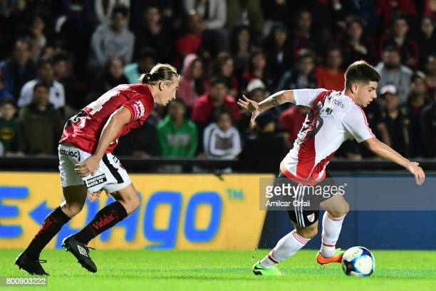 Tomas Andrade of River Plate drives the ball followed by Adrian Bastia of Colon during a match between Colon and River Plate as part of Torneo...