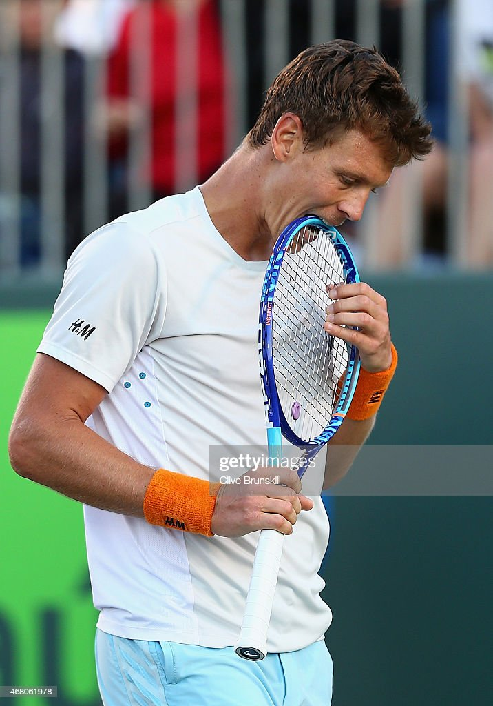 Tomas Berdych of the Czech Republic bites his racket in frustration whilst playing against Bernard Tomic of Australia in theiir third round match...