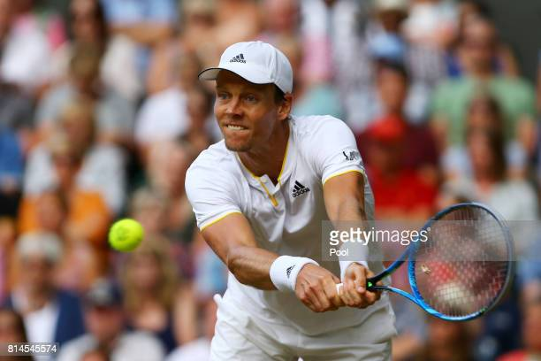 Tomas Berdych of The Czech Republic plays a backhand during the Gentlemen's Singles semi final match against Roger Federer of Switzerland on day...