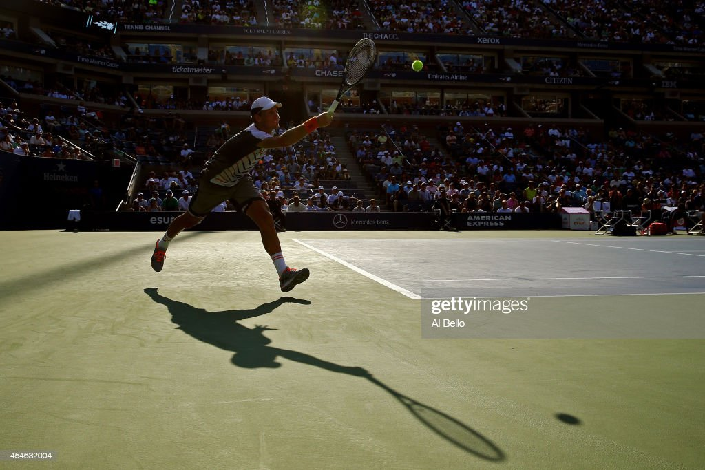 Tomas Berdych of the Czech Republic returns a shot to Marin Cilic of Croatia during their men's singles quarterfinal match on Day Eleven of the 2014...