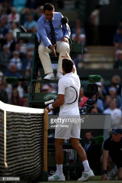 Tomas Berdych of The Czech Republic shake hands with the chair umpire after his Gentlemen's Singles quarter final match as opponent Novak Djokovic of...