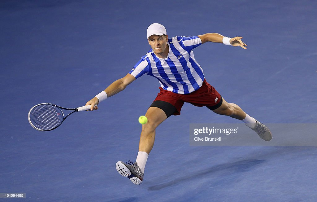 Tomas Berdych of the Czech Republic stretches to play a forehand during in his semifinal match against Stanislas Wawrinka of Switzerland during day...