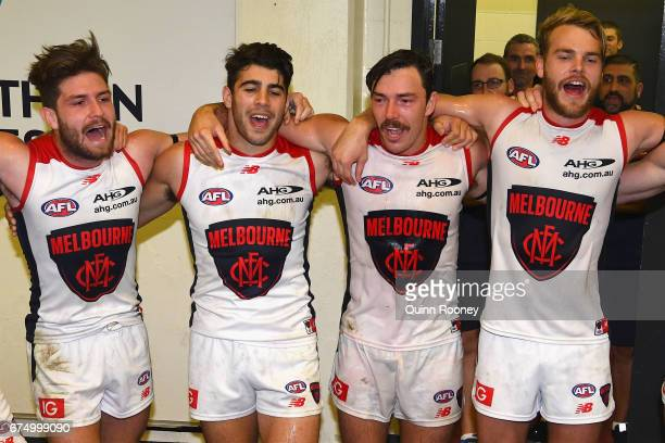 Tomas Bugg Christian Petracca Michael Hibberd and Jack Watts of the Demons sing the song in the rooms after winning the round six AFL match between...