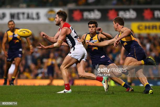 Tomas Bugg of the Demons handballs during the round 14 AFL match between the West Coast Eagles and the Melbourne Demons at Domain Stadium on June 24...