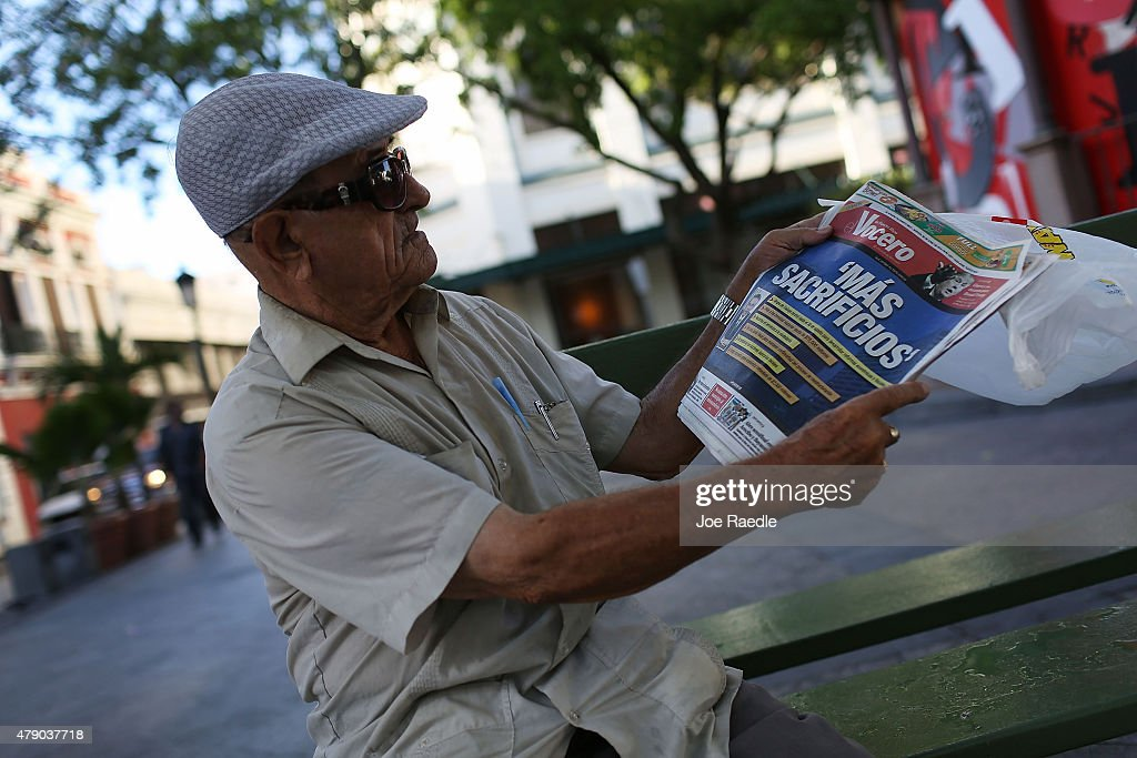 Tomas Colon reads a newspaper with a Spanish headline that reads 'more sacrifices' a day after the speech Puerto Rican Governor Alejandro Garcia...