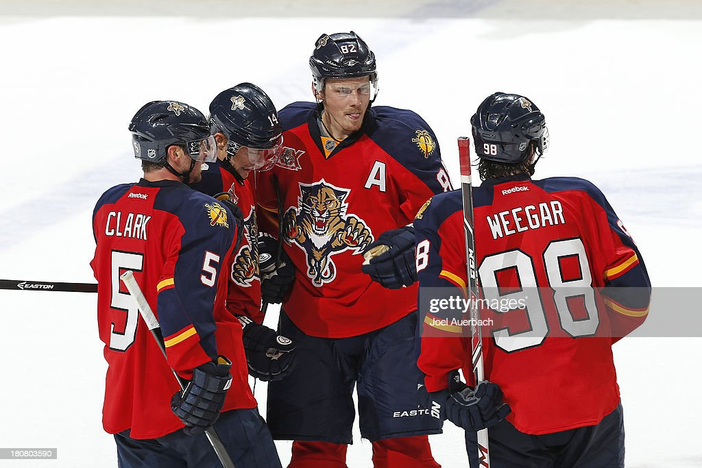Tomas Fleischmann #14 is congratulated by Brett Clark #5, Tomas Kopecky #82, and MacKenzie Weegar #98 of the Florida Panthers after scoring the game winning goal in overtime against the Nashville Predators during a preseason game at the BB&T Center on September 16, 2013 in Sunrise, Florida. The Panthers defeated the Predators 3-2 in overtime.