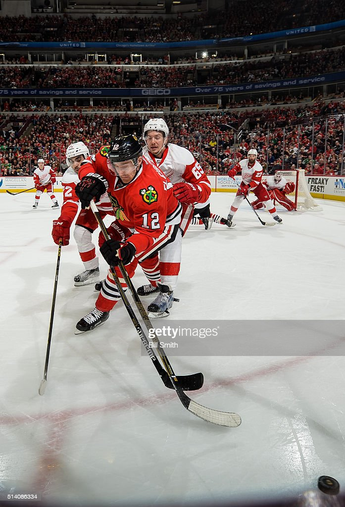 Tomas Fleischmann #12 of the Chicago Blackhawks chases the puck against Andreas Athanasiou #72 and Danny DeKeyser #65 of the Detroit Red Wings in the third period of the NHL game at the United Center on March 6, 2016 in Chicago, Illinois.