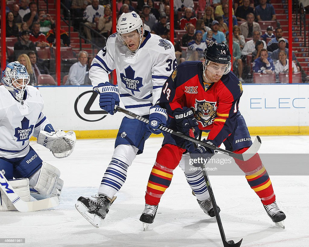 Tomas Fleischmann #14 of the Florida Panthers and Carl Gunnarsson #36 of the Toronto Maple Leafs battle for control of the puck during first-period action at the BB&T Center on February 4, 2014 in Sunrise, Florida.
