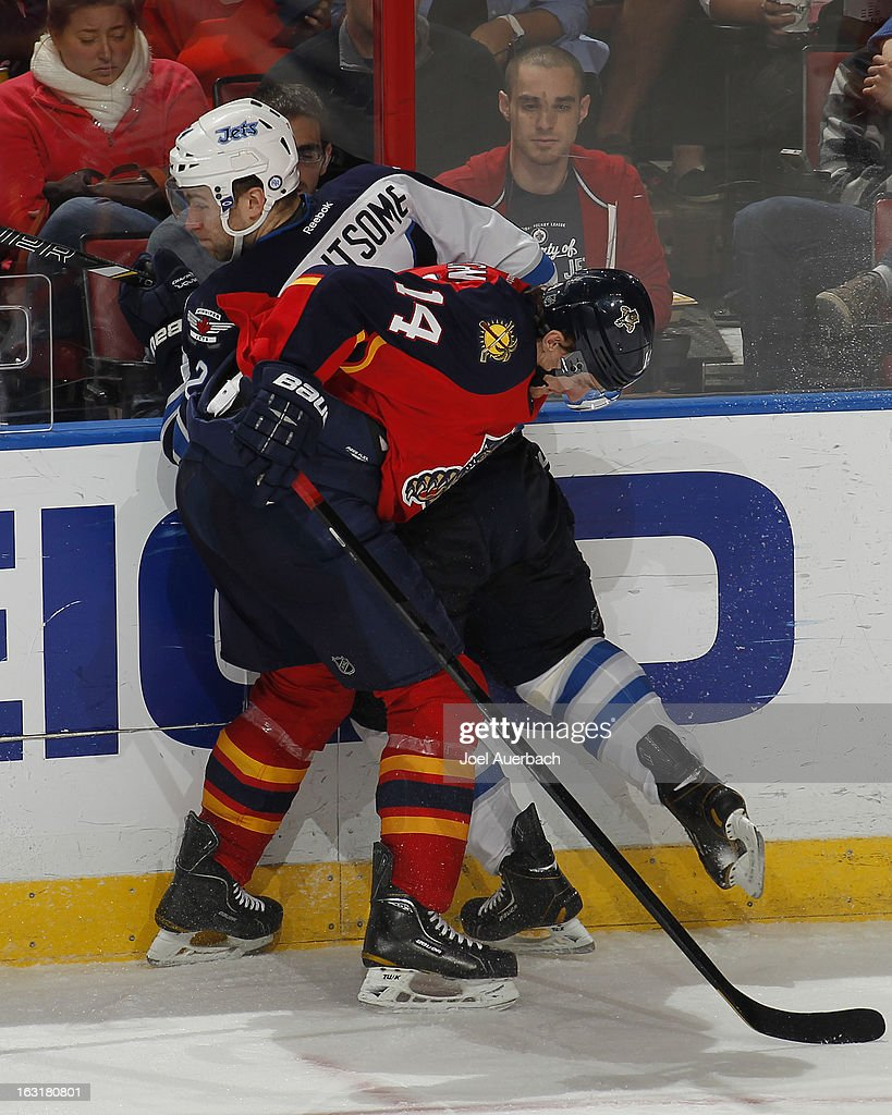 Tomas Fleischmann #14 of the Florida Panthers checks Grant Clitsome #24 of the Winnipeg Jets off the puck at the BB&T Center on March 5, 2013 in Sunrise, Florida. The Panthers defeated the Jets 4-1.