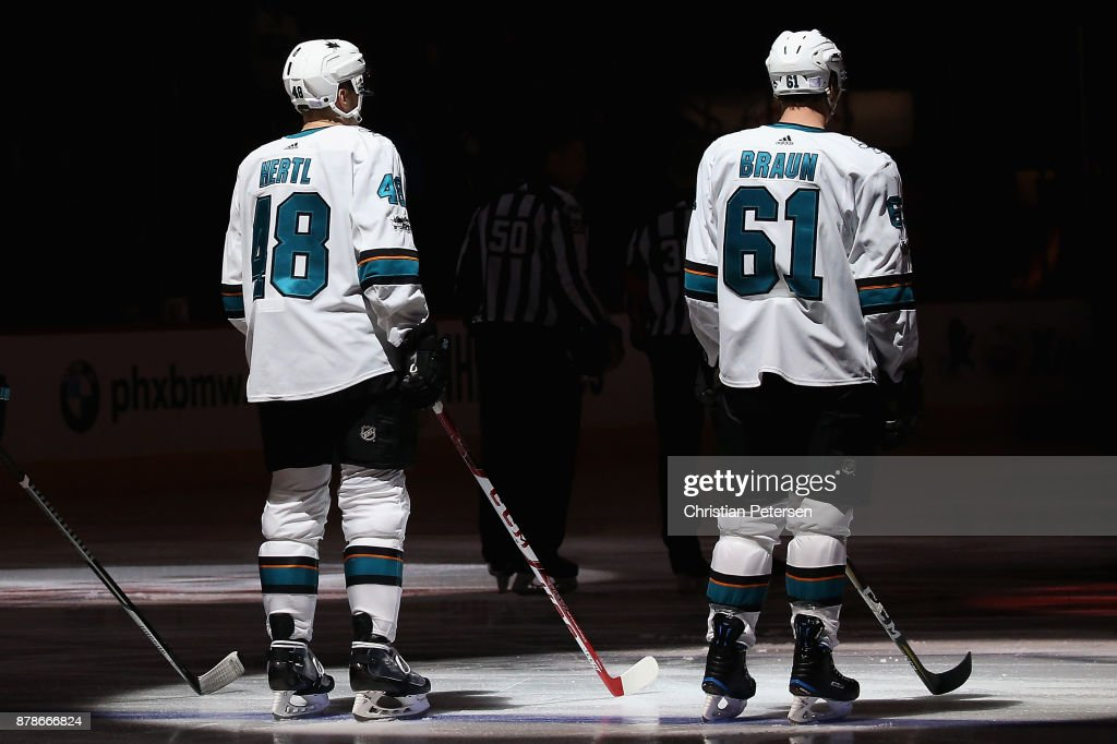Tomas Hertl #48 and Justin Braun #61 of the San Jose Sharks stand for the national anthem before the NHL game against the Arizona Coyotes at Gila River Arena on November 22, 2017 in Glendale, Arizona. The Sharks defeated the Coyotes 3-1.