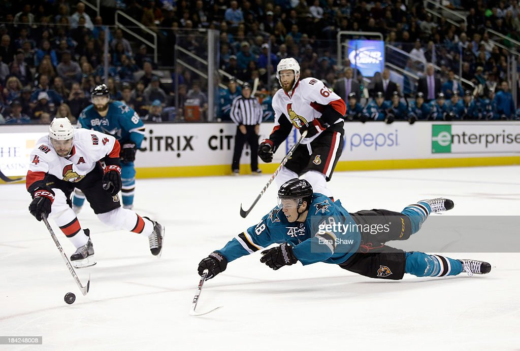 <a gi-track='captionPersonalityLinkClicked' href=/galleries/search?phrase=Tomas+Hertl&family=editorial&specificpeople=8761287 ng-click='$event.stopPropagation()'>Tomas Hertl</a> #48 of the San Jose Sharks and Chris Phillips #4 of the Ottawa Senators go for the puck at SAP Center on October 12, 2013 in San Jose, California.