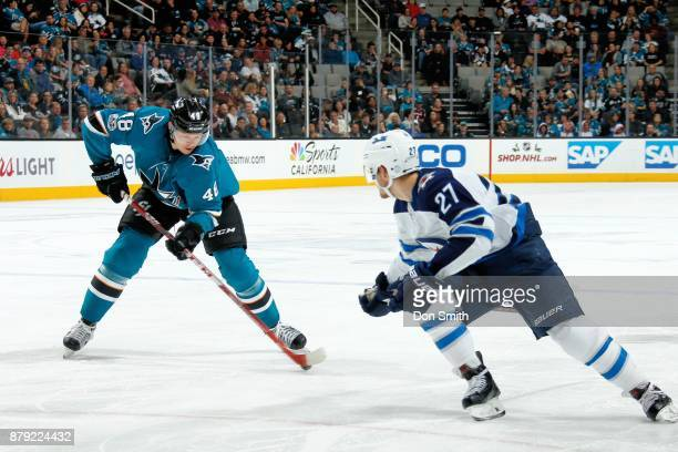 Tomas Hertl of the San Jose Sharks keeps the puck from Nicklaj Ehlers of the Winnipeg Jets at SAP Center on November 25 2017 in San Jose California