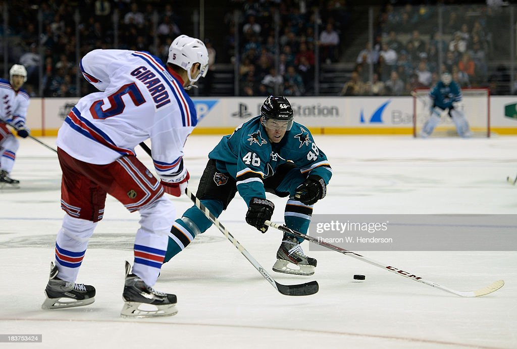 Tomas Hertl #48 of the San Jose Sharks skates and defends Dan Girardi #5 of the New York Rangers during the second period at SAP Center on October 8, 2013 in San Jose, California.