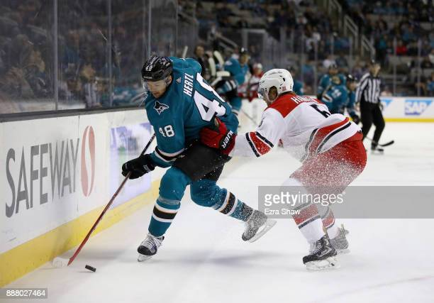 Tomas Hertl of the San Jose Sharks tries to keep the puck away from Noah Hanifin of the Carolina Hurricanes at SAP Center on December 7 2017 in San...