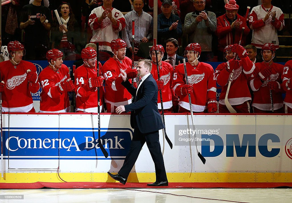 Tomas Holmstrom high fives teammates as he heads out for a ceremonial puck drop after announcing his retirement from the NHL earlier in the day prior to the Detroit Red Wings playing the Dallas Stars at Joe Louis Arena on January 22, 2013 in Detroit, Michigan. Holmstrom played 15 years for the in the NHL all for the Detroit Red Wings.