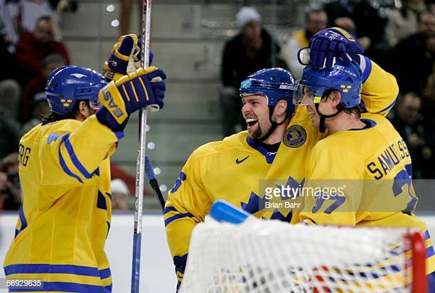 Tomas Holmstrom of Sweden celebrates with his teammates Mikael Samuelsson and Henrik Zetterberg after he scored the seventh goal in the third period...