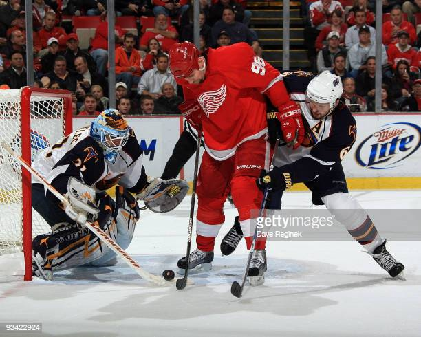 Tomas Holmstrom of the Detroit Red Wings and Ron Hainsey of the Atlanta Thrashers battle for the loose puck as teammate Ondrej Pavelec gets into...