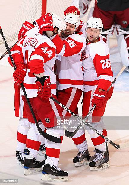 Tomas Holmstrom of the Detroit Red Wings celebrates with teammates Todd Bertuzzi and Brian Rafalski after Holmstrom scored a first period goal...