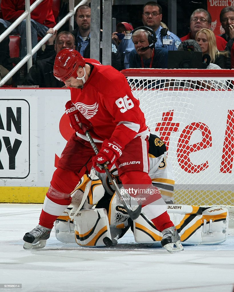 Tomas Holmstrom #96 of the Detroit Red Wings look for the loose puck as Tim Thomas #30 of the Boston Bruins gets into position during a NHL game at Joe Louis Arena on November 3, 2009 in Detroit, Michigan. Detroit defeated Boston 2-0.